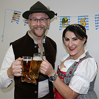 Chamber executive and board president toast with beers while wearing traditional German clothing